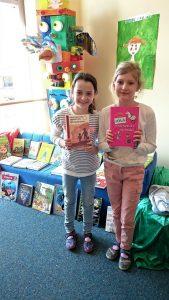Die Lesebesten der 4. Klassen, Anna Meena/4b und Leonie /4cfreuensich über ein Buch als Siegprämie.